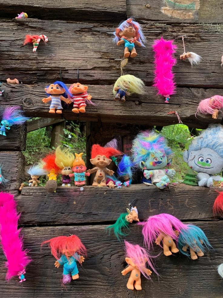 Troll toys nailed to wooden bridge