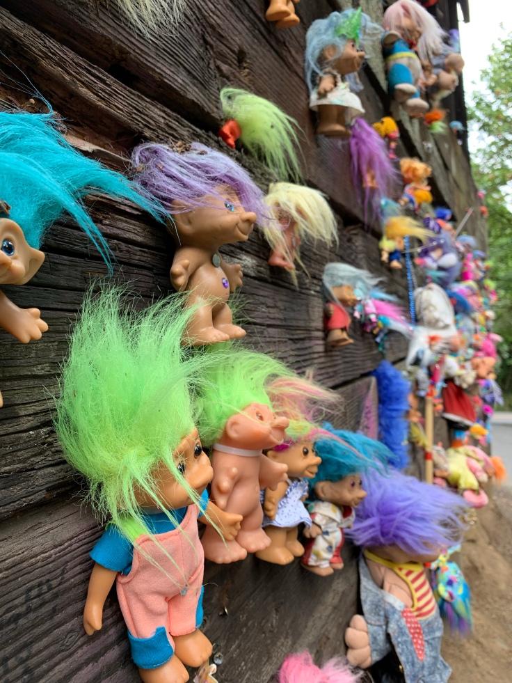 Troll toys nailed to wooden railroad bridge
