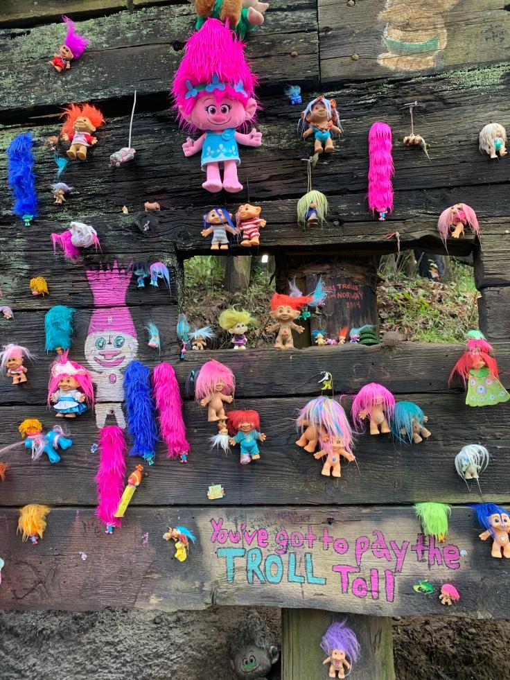Troll dolls nailed to wooden railroad trestle in Portland Oregon