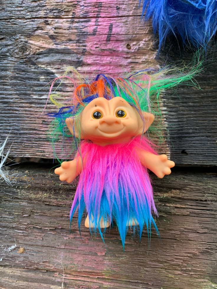 Troll toy with rainbow hair and fur suite