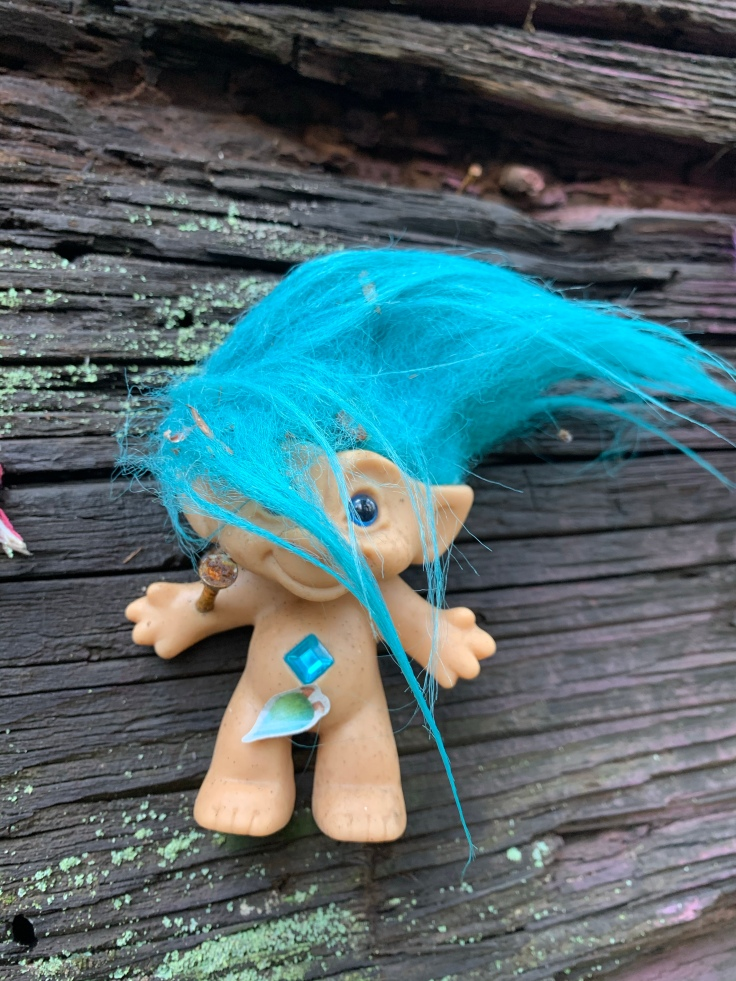 Troll doll with blue hair and blue belly jewel