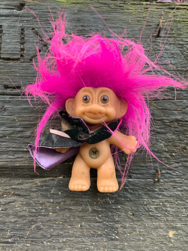 Troll with pink hair wearing black cape